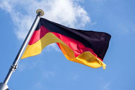 the view from below: German flag fluttering in the wind against the blue sky with light clouds, diagonal view from below, soft motion blur