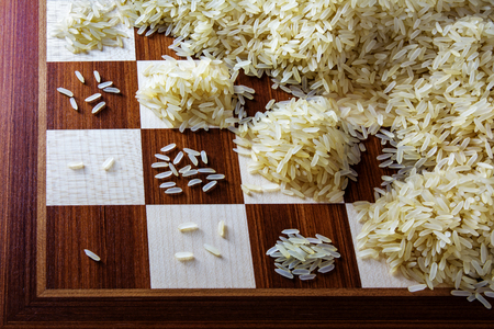 exponential: chessboard with exponential growing heaps of rice grains, concept of unlimited growth