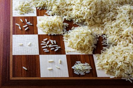 schaakbord met exponentieel groeiende afvalbergen van rijstkorrels, concept van de onbeperkte groei Stockfoto