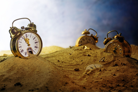 eventide: sand running out of a nostalgic alarm clock, other watches sink into the sand, surreal metaphor in a fantasy landscape, concept of time passes by, eventide or infinity, selected focus, very shallow depth of field Stock Photo