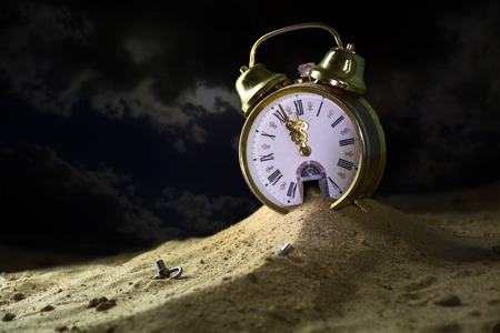sand running down from the door of a alarm clock in a fantasy desert at night, surreal metaphor, concept of time goes by, insomnia or infinity, selected focus, narrow depth of field Stock Photo