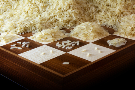 chessboard with growing heaps of rice grains, legend about the exponential function and unlimited growth, selected focus, narrow depth of field