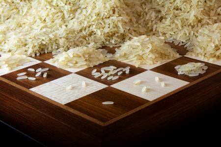 Schachbrett mit wachsenden Haufen von Reiskörnern, Legende über die Exponentialfunktion und unbegrenztes Wachstum, ausgewählten Fokus, schmalen Schärfentiefe Lizenzfreie Bilder