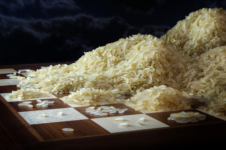 chessboard with growing heaps of rice grains, legend metaphor of exponential function and unlimited growth, dark sky with copy space, selected focus, narrow depth of field