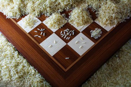 exponential: chessboard with growing heaps of rice grains, view from above showing the exponential function and unlimited growth, selected focus