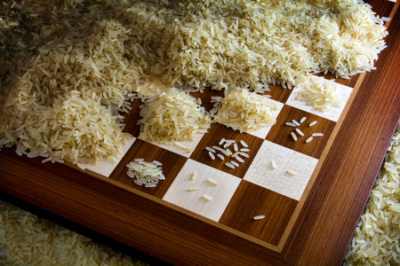 chessboard with exponential growing heaps of rice grains, legendary metaphor of unlimited growth Archivio Fotografico