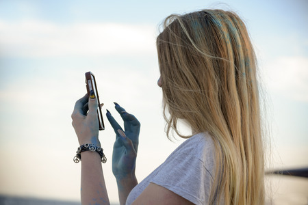 blond young woman with blue color in the hair and on the hands and very long ornamented fingernails typing in their mobile phone, in profile against the sky, copy space 스톡 콘텐츠