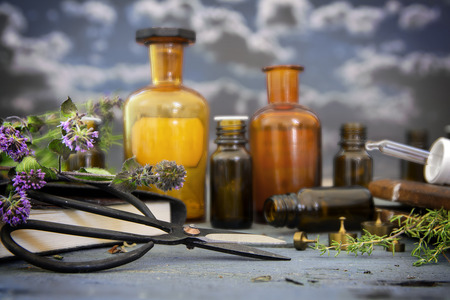 natural medicine, healing herbs, scissors and apothecary bottles on blue rustic wood against a dark sky with clouds, selected focus and narrow depth of field