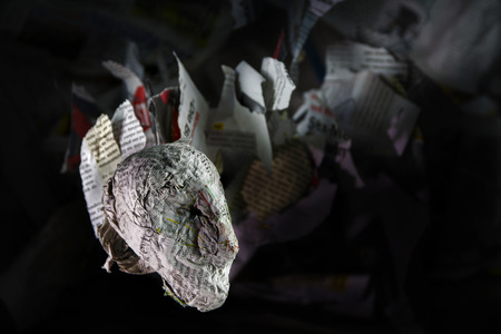 head of papier mache with a tail from flying newspaper snippets against a dark background with copy space, concept of news, information flood, journalism or rumors, selected focus Stock Photo
