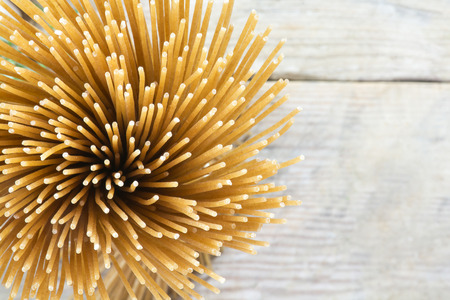 bunch of wholegrain spaghetti from above on a blurry background from rustic gray wood with copy space, closeup with selected focus and a very narrow depth of field