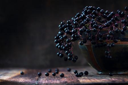 Black vlierbessen bos (Sambucus nigra) in een oude klei kom en sommige bessen op een rustieke houten tafel tegen een donkere achtergrond met kopie ruimte, low key vintage stilleven, close-up met geselecteerde focus en extreem smalle scherptediepte