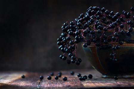 Black elderberries bunch (Sambucus nigra) in an old clay bowl and some berries on a rustic wooden table against a dark background with copy space, low key vintage still life, closeup with selected focus and extremely narrow depth of field