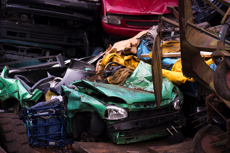 scrap car: colors on the junkyard, crushed turquoise scrap car, yellow garbage and a red junk car between the brown metal waste, concept for insurance or waste management Stock Photo