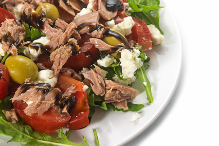 tuna salad with tomatoes, olives and arugula, recipe in Mediterranean style, white plate on a white background, close up