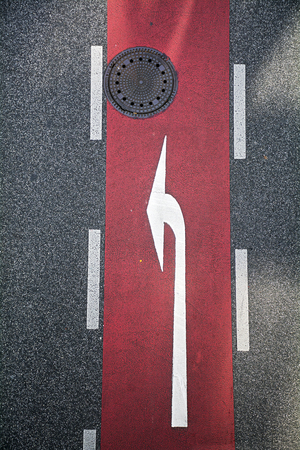 gully: Asphalt road with red marked trail and white arrow, as well as a gully cover, top view from above