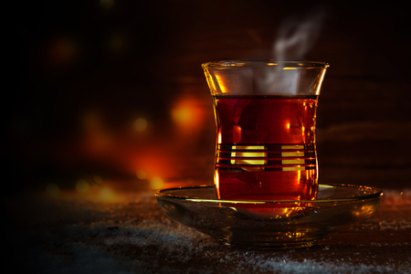 Cup of Turkish tea on saucer on rustic wood with snow in front of a dark blurred background with red and golden bokeh lights, copy space, selected focus, narrow depth of field Stock Photo