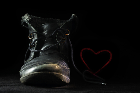 Old worn out black shoe in love forms a blushing red heart with its shoelace against a dark background, concept for late love in old age, fidelity or a special greeting card for valentines day, selective focus