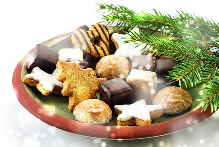 Christmas cookies, traditional gingerbread cakes, cinnamon stars and pepper nuts on a plate with fir branches and blurred snowy lights on a bright background, selected focus, narrow depth of field