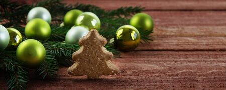 Green christmas baubles  in fir branches and a small Christmas tree made of gingerbread on a rustic wooden table, banner or website header with copy space, selected focus, narrow depth of field