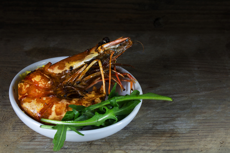 roasted black tiger prawn with rocket salad as a mediterranean appetizer on a rustic wooden background, close up with selected focus, narrow depth of field, copy space Stock Photo