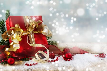 christmas and new year gift with red paper, golden ribbons and baubles in the snow on a rustic wooden plank, blue background with bokeh lights and copy space