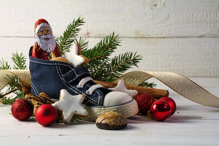 Kinderschuhe, gefüllt mit Süßigkeiten, Plätzchen und Weihnachtsdekoration für Nicholas Tag am 6. Dezember in Deutschland vor weißem rustikalem Holz mit Kopie Raum, selektiver Fokus, schmalen Schärfentiefe