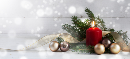 Red burning candle with christmas decoration, fir tree, baubles and golden ribbon, in front of a white  wooden wall with bokeh lights and generous copy space, panorama, selective focus, narrow depth of field