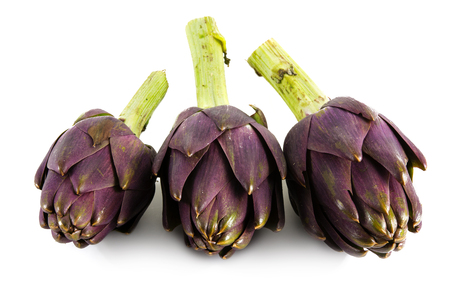three purple artichokes from italy isolated on a white background, close up with selective focus and narrow depth of field