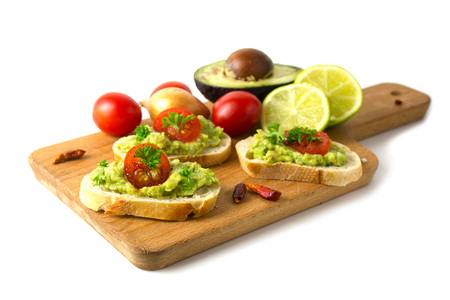 Canapes with avocado cream or guacamole and tomatoes freshly prepared with ingredients on a kitchen board, isolated on a white background, healthy party snack, selected focus, narrow depth of field
