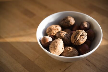 Fresh walnuts in a white bowl on a wooden table, copy space, selective focus, narrow depth of field