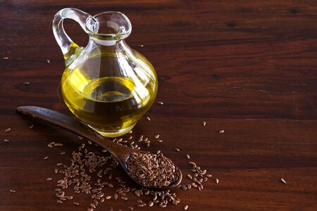 flax seeds on a spoon and linseed oil in a glass jug on a dark wooden table, copy space