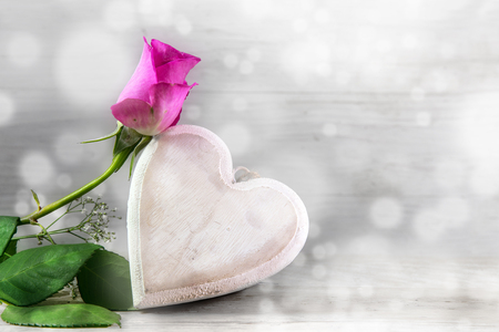 Pink rose and a wooden heart against a light gray bokeh background with copy space, love concept for mothers day and valentines day, selected soft focus, narrow depth of field Stock Photo