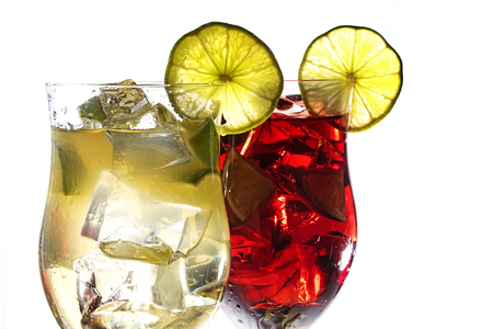 Two cocktail glasses, green and red mixed drinks of  juice, berries, lime and ice, with or without alcohol, isolated on a white background, closeup, selected focus, narrow depth of field Stock Photo