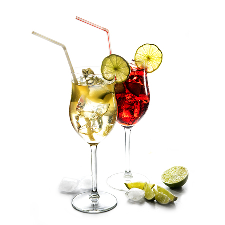 cocktail glasses: Two cocktail glasses, yellow and red mixed drinks from juice, lime and ice, with or without alcohol, isolated on a white background, selected focus, narrow depth of field