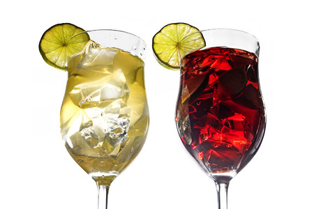 cocktail glasses: Two cocktail glasses with white and red mixed drinks from lime, cherries, berries, grapefruit and ice, with or without alcohol, isolated on a white background, selected focus, narrow depth of field, Stock Photo