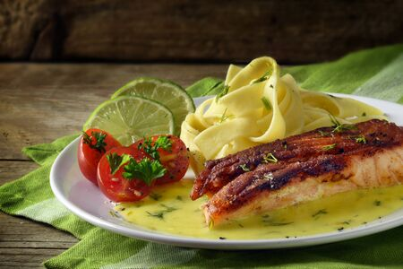 Grilled salmon dish with saffron sauce and tagliatelle pasta, lime, tomatoes and dill garnish on a green napkin on a rustic wooden table, copy space, selective focus, narrow depth of field Stock Photo