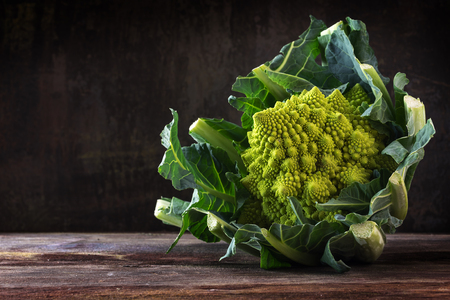 Romanesco broccoli or Roman cauliflower on a rustic table from dark wood,  the healthy vegetable Brassica oleracea is a variation of cauliflower bred near Rome, copy space,
