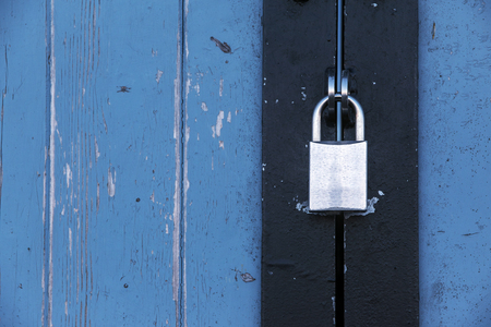 savety: Silver padlock on an old blue wooden door, concept background with copy space Stock Photo