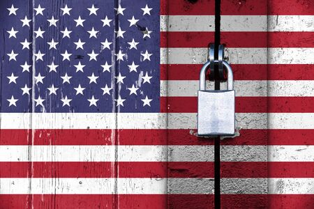 protectionism: United states of america flag on a wooden door locked with a padlock, concept background with copy space