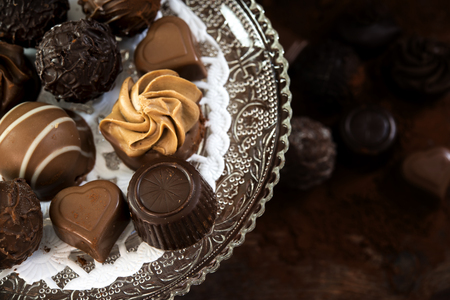 chocolate pralines on an étagère of glass and further blurred underneath on dark rustic wood, close up from above, selected focus, narrow depth of field