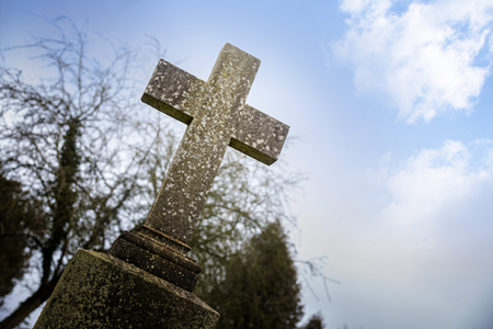 christian halloween: weathered stone cross or gravestone against the blue sky, memorial day concept for war dead or religious christian symbol for holiday like good friday, easter and pentecost, also used for halloween