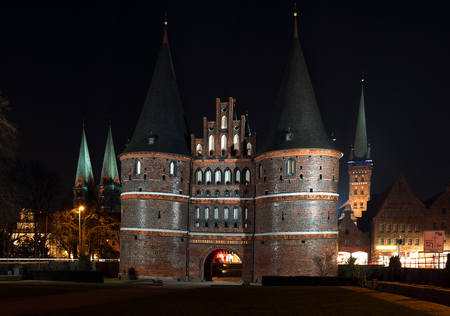 iluminated: Holstentor and church towers in Luebeck iluminated at night, the medieval city gate is a popular tourist attraction of the historic old town in Schleswig-Holstein, Germany Stock Photo