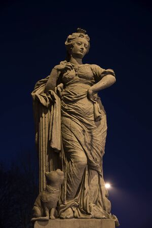 Freedom figure at night, allegorical sculpture from sandstone from the 18th century on the doll bridge called Puppenbruecke in Luebeck, tourist attraction in north germany, copy space in the dark sky