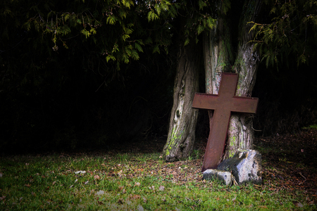 transience: Rusty cross made of metal leaning against old tree trunks in shadow under the tops, religious christian symbol for death, Good Friday and Easter or creepy halloween concep