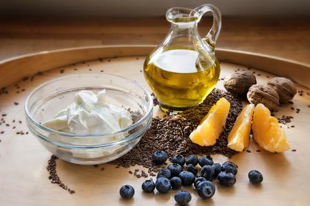 Gezond ontbijt met kwark of cottage cheese, flaxsamen, lijnolie en vers fruit op een houten plank, vetzuren in de voeding met omega-3, geselecteerde focus, smalle diepte van het veld