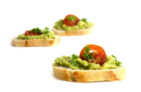 canapes with avocado cream or guacamole and tomatoes isolated on a white background, healthy party sandwiches, closeup, selected focus, narrow depth of field Stock Photo