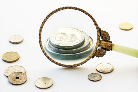 savety: Capital increase, vintage magnifying glass enlarge a few coins, bright gray background, financial concept, selected focus, narrow depth of field Stock Photo