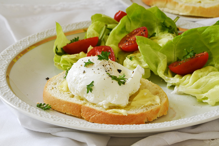 Poached egg on baguette slice with salad and tomatoes on a white plate, delicious breakfast or snack, selective focus, narrow depth of field Stock Photo