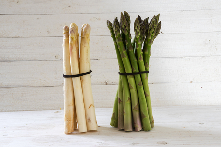 Asparagus, a green and a white bunch stand on a white painted wooden background, copy space, selective focus