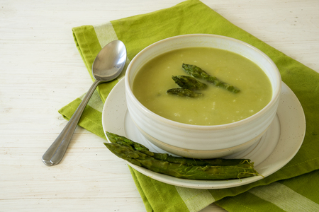 creativ: soup from green asparagus in a bowl on a green napkin and a white wooden table, copy space, selected focus, narrow depth of field